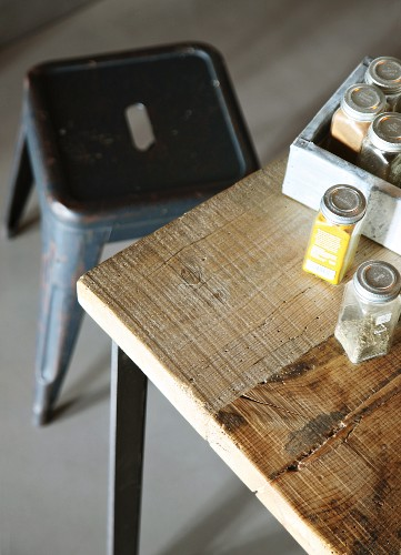 Jars of herbs in partially visible crate on wooden table with retro metal stool in background