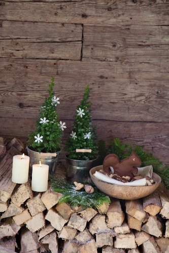 Hand-crafted felt squirrel in wooden bowl of nuts on festively decorated stack of firewood against cabin wall