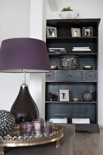 Purple table lamp on coffee table in front of black shelving unit