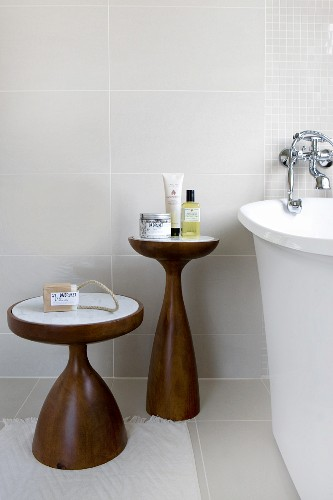 Two-part set of wooden side tables with marble tops against pale grey wall tiles in modern bathroom