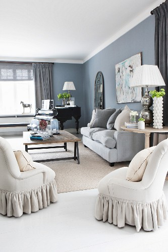 Elegant living room with upholstered furniture and black piano in background