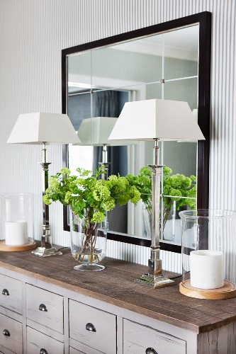 Elegant silver table lamps with white lampshades on grey apothecary cabinet below framed mirror in elegant interior