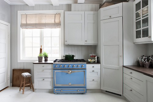 White, Scandinavian country-house kitchen with pale blue gas cooker and vintage ambiance