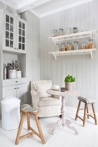 Armchair, table and wooden stools in corner of Scandinavian country-house kitchen