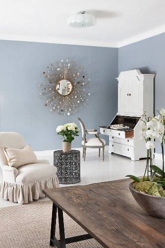 White bureau and wall mirror in corner of living room; bowl of orchids on rustic table in foreground