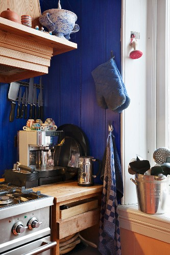 Blue-painted wooden wall and coffee machine on solid wooden base units in corner of kitchen
