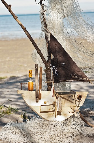 Boat sculpture made from flotsam on sandy beach