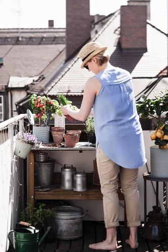 Frau bepflanzt Tontöpfe an Pflanztisch auf Dachterrasse