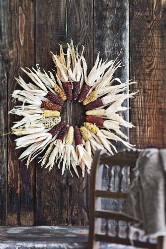 Wreath of decorative maize cobs on board wall