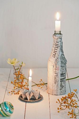 Weihnachtliche Tischdeko: Gefalteter Kerzenhalter und Flasche ummantelt mit Zeitungspapier