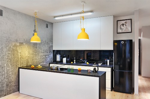 Open-plan fitted kitchen with yellow pendant lamps and photo wall mural of New York skyline in pale grey