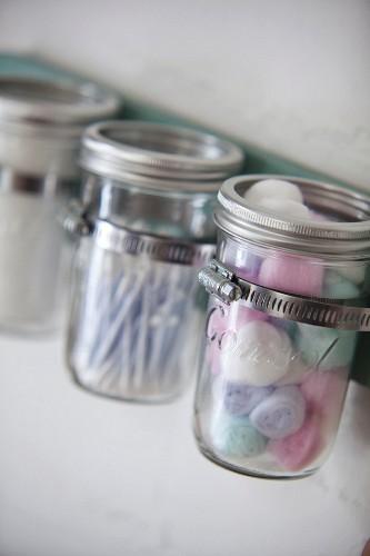 Cosmetic utensils in retro screw-top jars in metal rack mounted on wall