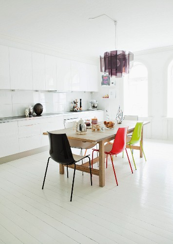 Accents of colour provided by ceiling lamp and dining chairs in spacious white kitchen in period apartment