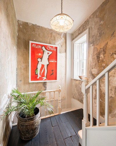 Palm in vintage pot on landing with retro film poster on patinated wall