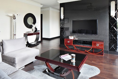 Elegant interior with Art Deco furniture, pale grey sofa set around coffee table and mahogany sideboard against dark grey partition