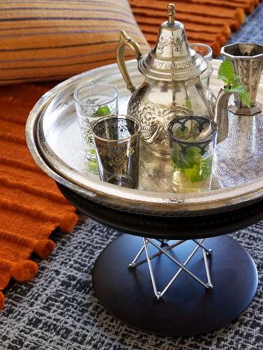 Moroccan teapot and tea glasses on silver tray on modern side table