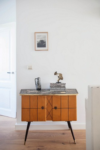 Pale, wooden retro cabinet against white wall