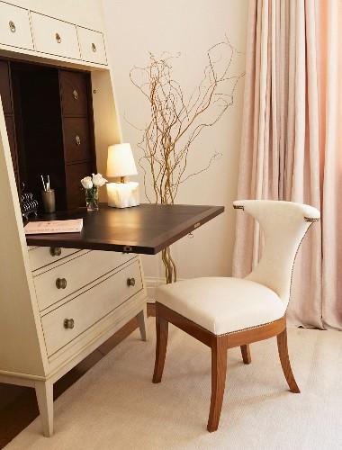 Elegant, feminine writing area with elegant bureau and upholstered chair