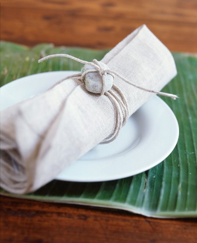 Linen napkin decorated with pebble on white plate on banana leaf used as place mat