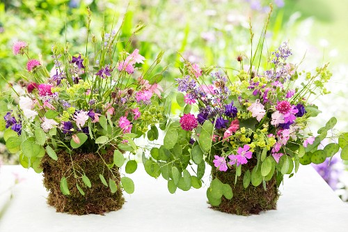 Posies of aquilegia and lady's mantle in DIY vases wrapped in moss