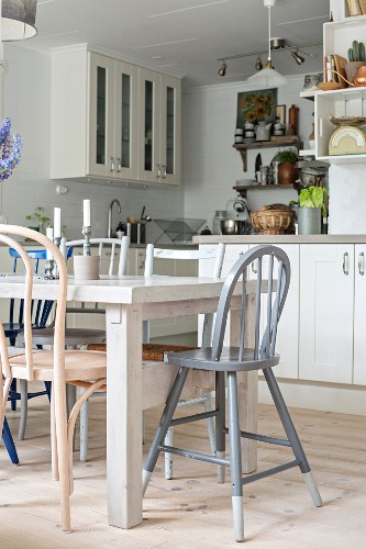 Various chairs around white-painted dining table in fitted kitchen with white-painted, country-house-style kitchen cabinets