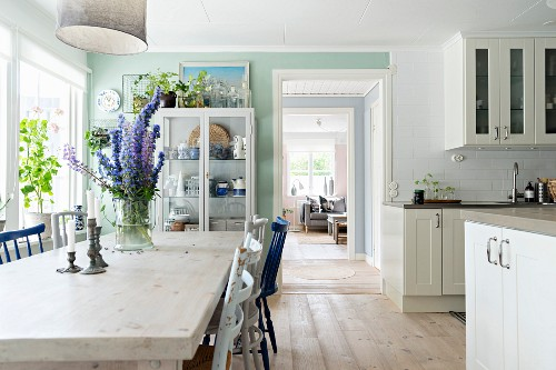 Dining area in spacious kitchen with white fitted cabinets and display case
