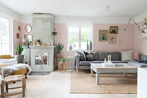 Corner couch, coffee table and fireplace in living room with pastel pink walls