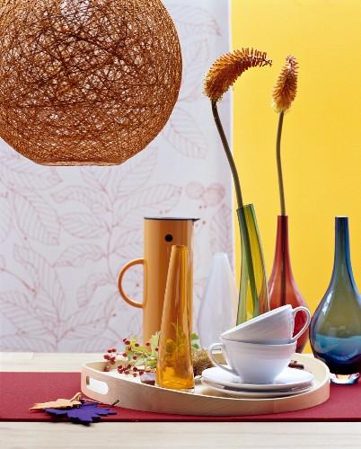 Geschirr, Vase und Thermoskanne auf Birkenholztablett