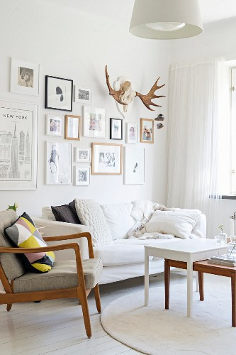 Fifties' armchair with wooden frame, set of coffee tables and sofa below pictures and antlers on wall