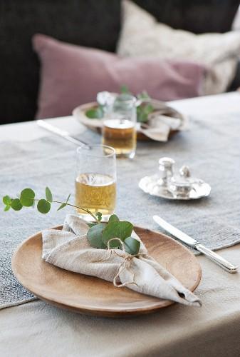 Linen napkin, eucalyptus sprig and wooden plate
