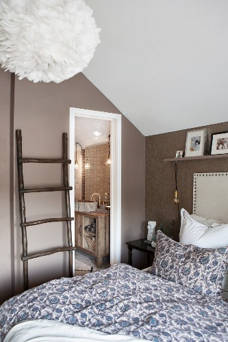 Attic bedroom with ladder used as clothes rack and view into bathroom