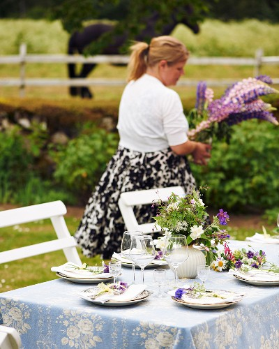 A garden table laid with meadow flowers for a mid-summer festival