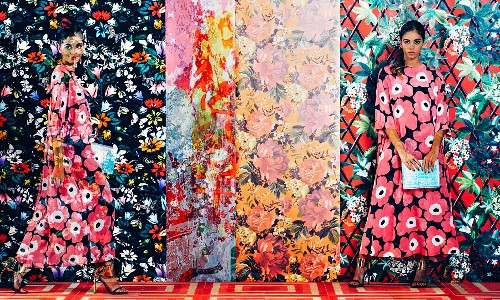 Young woman in a flower dress in front of different strips of wallpaper with different floral motifs