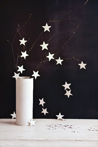 A twig decorated with glittery stars in a vase