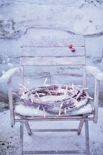 And ice decorative wreath with fairy lights on a snow-covered wooden chair