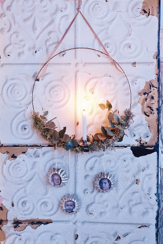 A wall wreath candle holder decorated with family photos