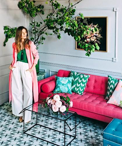 Junge Frau vor Kassetten-Wandverkleidung und pinkfarbenem Sofa mit türkisgrünen Kissen