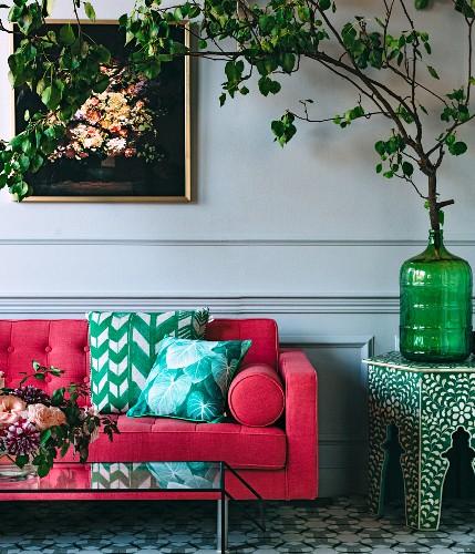 Pinkfarbenes Sofas mit Kissen, neben Blätterzweig in Glasvase