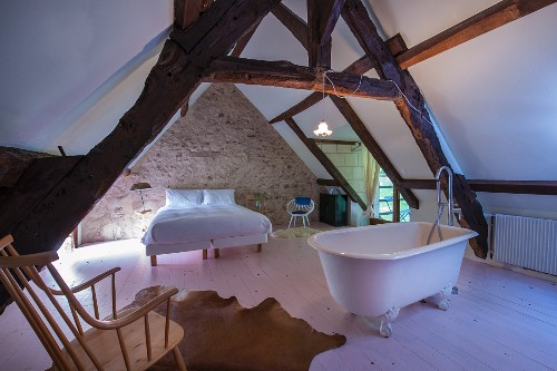 Free-standing bathtub, double bed and rustic exposed beams in converted attic
