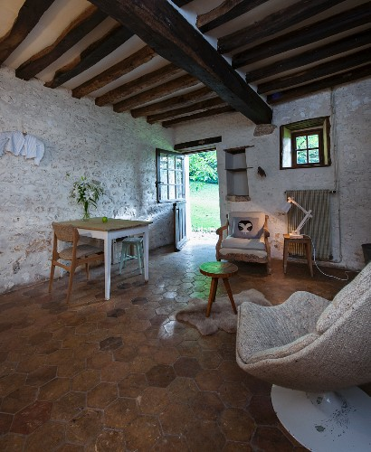 Tiled floor, painted stone wall and rustic wood-beamed ceiling in vintage interior