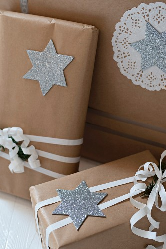 Christmas presents wrapped in brown paper decorated with silver stars and paper doilies