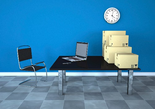 Office with blue wall, wall clock, laptop and shipping boxes on table