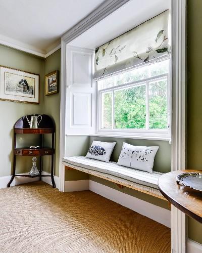 Window seat in large window niche next to antique quarter-round corner table