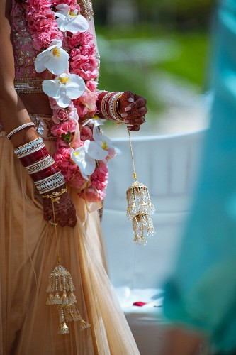 Indian wedding - woman adorned with flower garlands and with henna patterns on hands