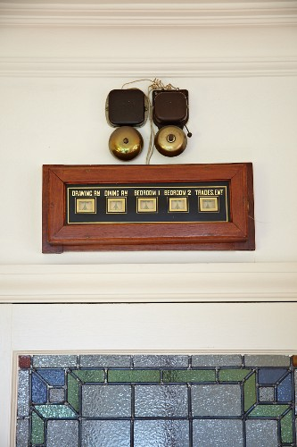 Vintage room-service bells with room display panel above blue and green stained glass interior door