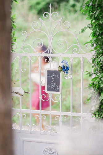 Blackboard with invitation to coffee party and floral decoration hung on romantic wrought-iron garden gate