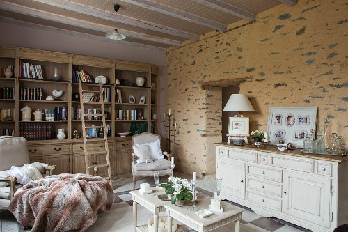 Bookcase, comfortable armchairs and white sideboard against rustic stone wall in country-house-style living room