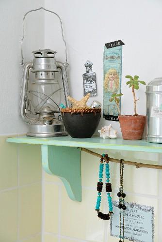Vintage-style ornaments and storm lamp on mint-green bracket shelf