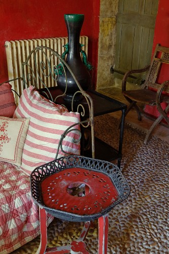 Rustic plant stand painted red next to daybed with ornate, vintage-style metal frame