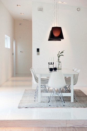 White classic chairs around white table below dark pendant lamps in contemporary interior